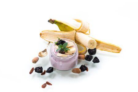 Sweet tasty yogurt with banana, prunes, raisins in a glass jar on a white