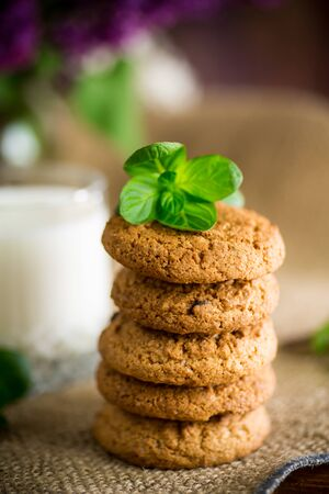 oatmeal cookies with a glass of fresh milk on a wooden table