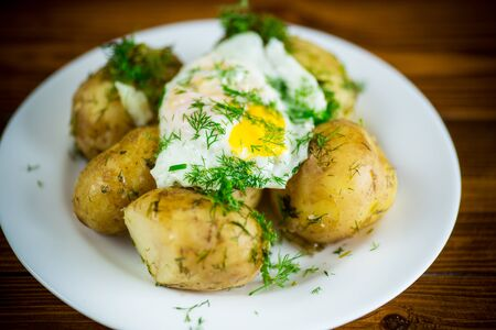 boiled early potatoes with fried egg and dill in a plate