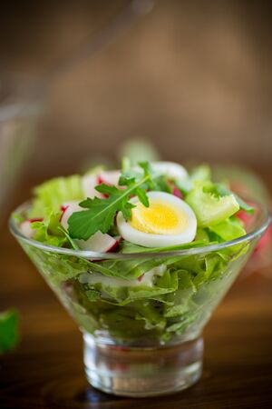spring salad with arugula, boiled eggs, fresh radish, salad leaves in a glass bowl on a wooden table