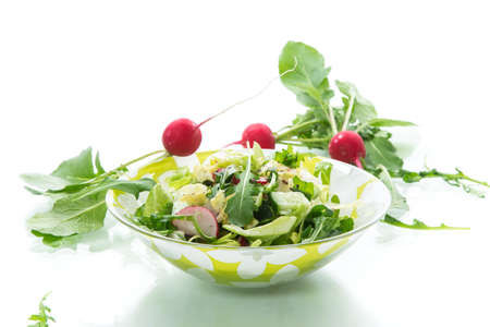 Spring salad from early vegetables, lettuce leaves, radishes and herbs in a plate isolated on white background