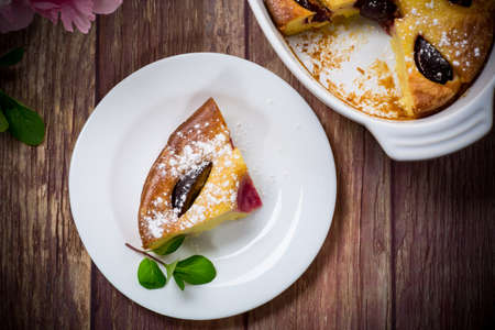 sweet homemade casserole with fruits inside in a plate on a wooden table