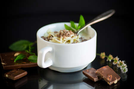 sweet noodles with milk and grated chocolate in a bowl on a black background