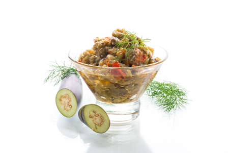 cooked summer eggplant caviar with vegetables in a bowl isolated on white background