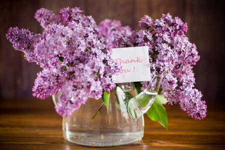 bouquet of beautiful spring lilac flowers on a wooden table