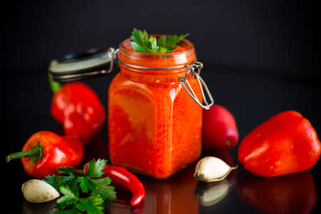 fresh natural homemade sauce made of peppers, tomatoes and other vegetables in a glass jar