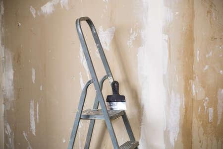 old stepladder on the background of plastered walls before renovation