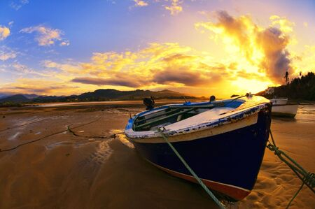 asturias: a boat rests on the sand during sunset in Villaviciosa, Asturias Stock Photo