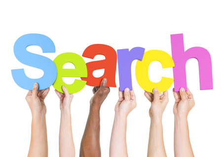 Multi-Ethnic Group Of People Holding The Word Search