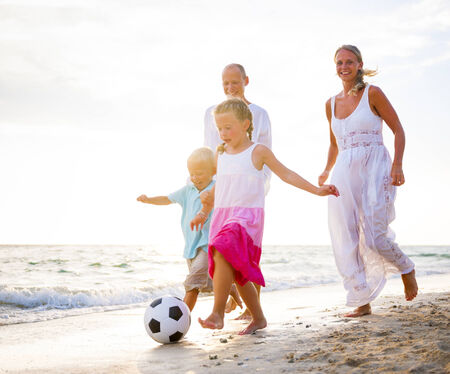 Blonde Family Playing Ball On The Beach photo
