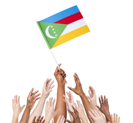 comoros: Group Of Multi-Ethnic People Reaching For And Holding The Flag Of Comoros