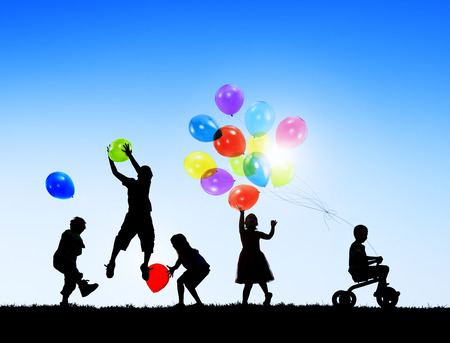 Silhouettes of Cheerful Children Playing Balloons Outdoors photo