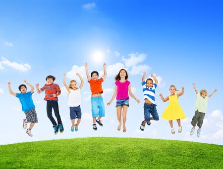 interacci�n: Grupo de diversa multi-ethinc Ni�os saltando al aire libre