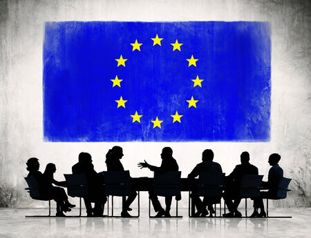 Business People Discussing Around The Conference Table And A Flag Of European Union Above  photo