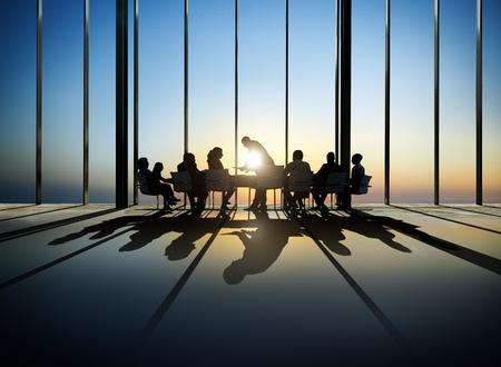 Groep van bedrijven rond de vergadertafel met een uitzicht op de zonsondergang
