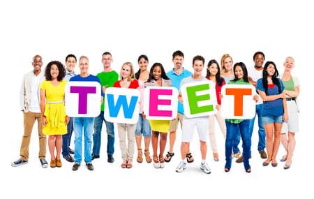 tweet: Multi-ethnic group of people holding 5 letters of placards forming tweet