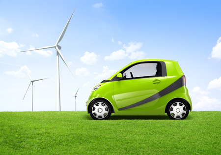 Electric green car in the outdoor with a view of windmill behind it  Stock Photo