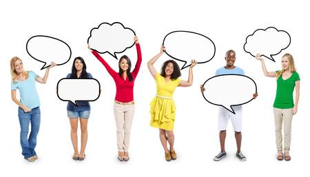 空白のスピーチの泡を保持している多民族の多様な人々
