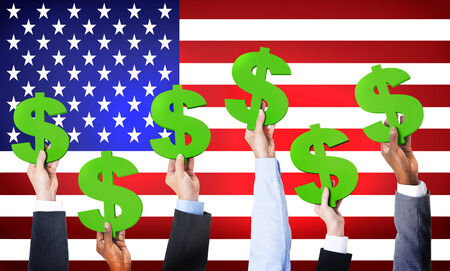 Multi-Ethnic Hands Holding Dollar Signs With Flag Of USA For The Background  photo