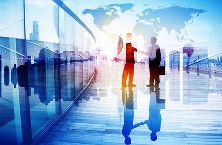 Silhouetten van twee zakenman schudden handen Stockfoto