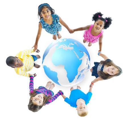 mundo manos: Multi�tnico ni�os de la mano alrededor del globo de Foto de archivo