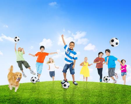 Multiétnico niños al aire libre que juega a fútbol juntos y un perro de mascota