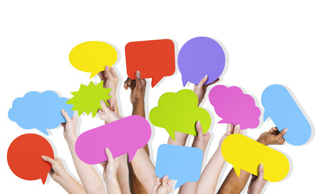 Group of human arms raised with multi colored speech bubble