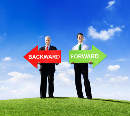 backward: Two Businessmen Holding Contrasting Arrows for Backward and Forward