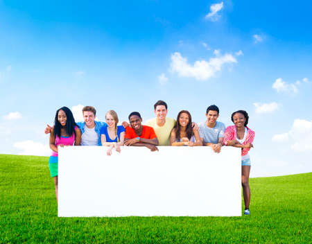 Group of teenagers posing with a white board on the hills  photo