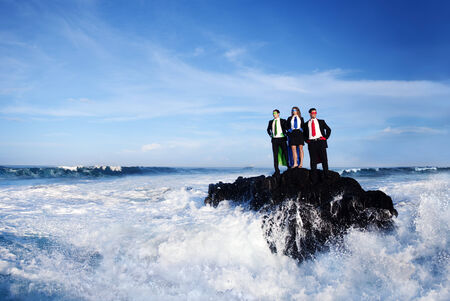 Business superheroes standing on a rock, in the middle of the sea