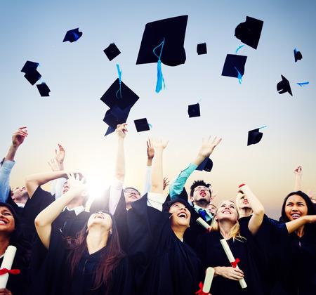birrete de graduacion: Estudiantes alegres que lanzan tapas de graduación en el aire