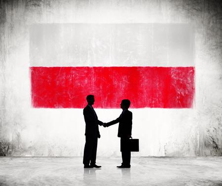 bandera de polonia: Dos hombres de negocios que sacuden las manos con la bandera polaca Como Fondo Foto de archivo