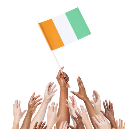 Group Of Multi-Ethnic People Reaching For And Holding The Flag Of Cote D photo