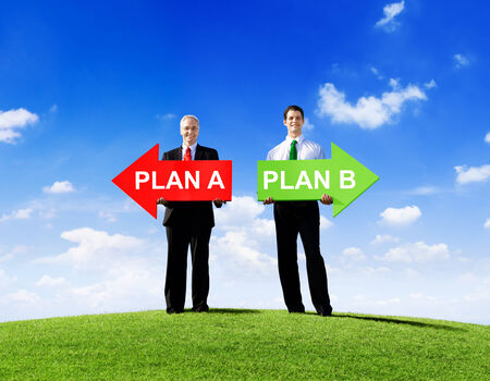 Two Businessmen Holding Contrasting Arrows for Plan A and Plan B  photo