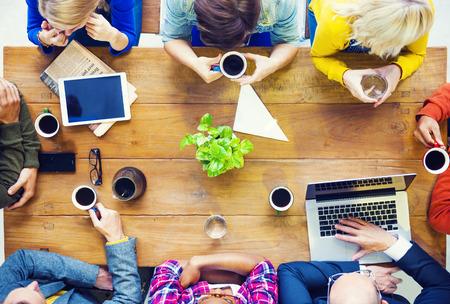 カフェで話してのスタートアップのビジネスを持つ多民族の人々