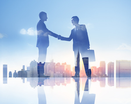 Silhouettes of Two Businessmen Having a Handshake photo