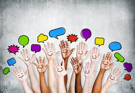 Multiethnic people arms raised with Speech Bubbles and Smiling Symbol photo