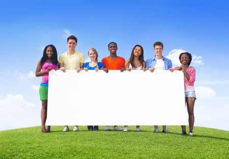 Multi-Ethnic Teenagers Holding Empty Billboard for Copy Space photo