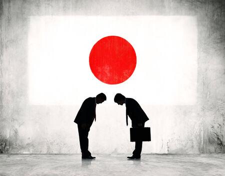 Twee Zakenlieden Buigen met Japan Vlag