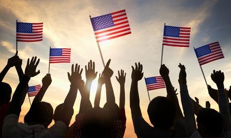 米国の旗を保持している人々 のシルエット