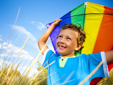 Cheerful Young Boy Playing Kite Outdoors photo
