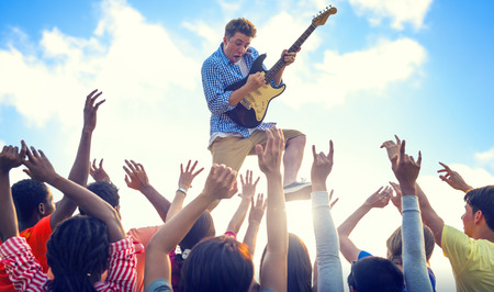 Young Man with a Guitar Performing on an Ecstatic Crowds photo