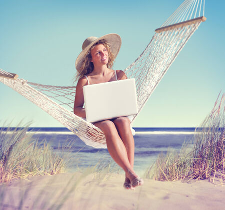 Beautiful Woman Sitting on a Hammock by the Beach Stock Photo