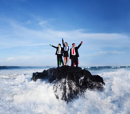 Three business people wearing superhero costumes posing on a rock with gushing waves