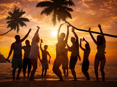 gente bailando: Grupo de personas de fiesta alegre en una playa