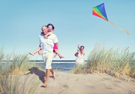 flying man: Cheerful Family Playing by the Beach