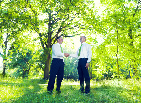 Green business handshake in the forest photo