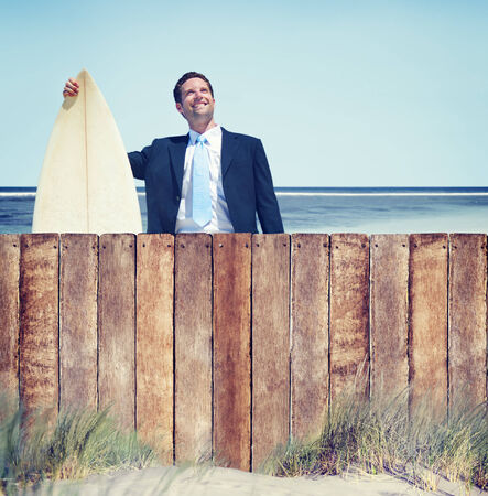 Businessman with Surfboard by the Beach photo