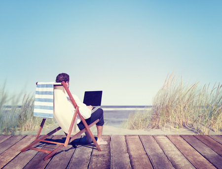 guy with laptop: Businessman Working by the Beach Stock Photo