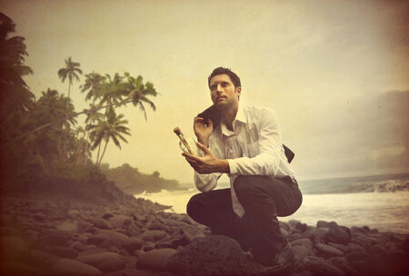 Businessman Shipwrecked on a desert island with message in a bottle  photo